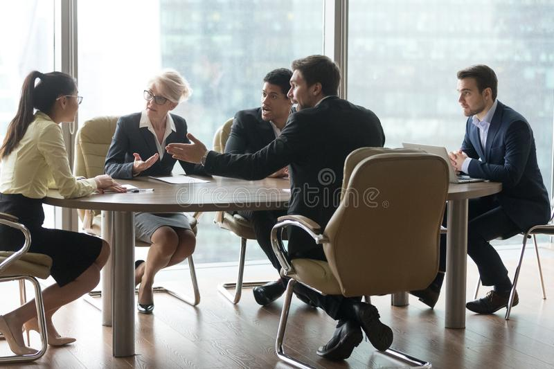 Multiracial team group disputing in office boardroom at meeting stock photos