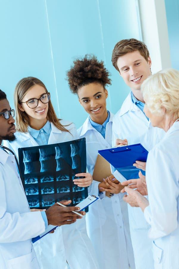 Multiracial grupa młodzi medyczni stażyści słucha starszej osoby lekarka w a obraz royalty free