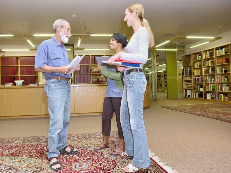 Multiracial grupa życzliwi ludzie gawędzi w bibliotece fotografia stock