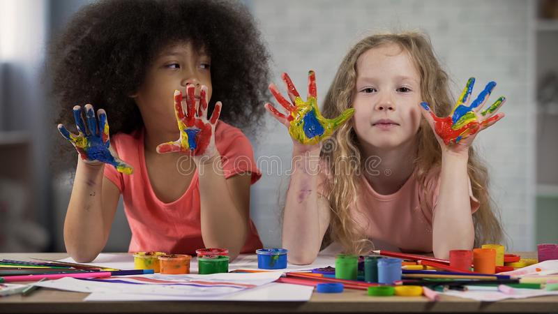 Multiracial kids visiting art lesson at club, palms in paints, happy childhood stock photos