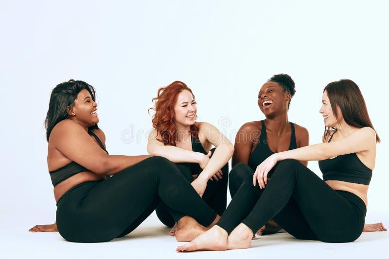 Multiracial kobiety z r??nym stojakiem wp?lnie, u?miechem rozmiaru i pochodzenia etnicznego i obraz stock
