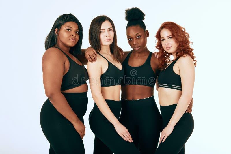 Multiracial kobiety z r??nym stojakiem wp?lnie, u?miechem rozmiaru i pochodzenia etnicznego i fotografia royalty free