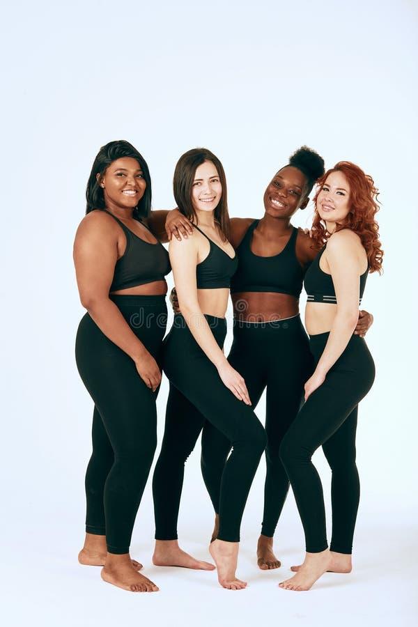 Multiracial kobiety z r??nym stojakiem wp?lnie, u?miechem rozmiaru i pochodzenia etnicznego i obraz royalty free