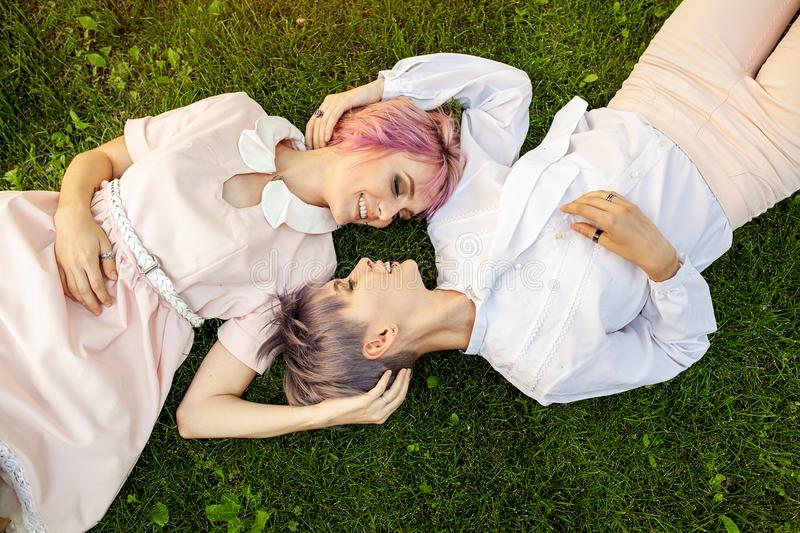 Multiracial lesbian couple lying on the grass. They are two young women resting at park. One is caucasian and the other is asian. royalty free stock photography