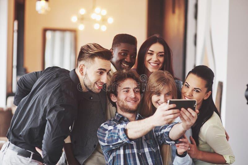 Multiracial ludzie ma zabawę przy kawiarnią bierze selfie z telefonem komórkowym Grupa młodzi przyjaciele siedzi przy restauracją fotografia royalty free