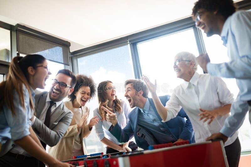 Multiracial ludzie ma zabawę w biurowym pokoju, z podnieceniem różnorodni pracownicy cieszy się aktywność przy pracą obraz stock
