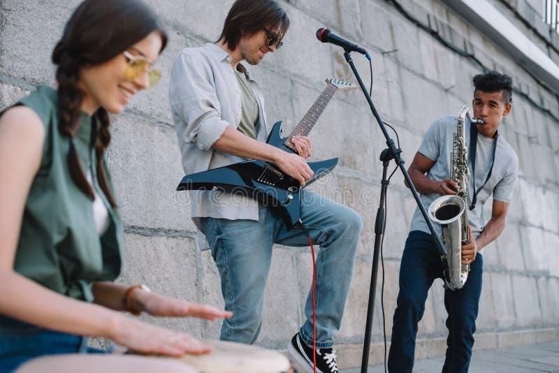 Multiracial młody muzykalny zespół z gitara saksofonu i bębenu spełnianiem fotografia royalty free