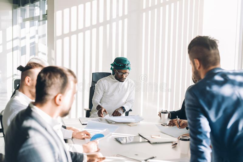 Multiracial male business executives discuss project sitting at conference table stock photography