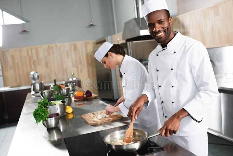 Multiracial male and female chefs team cooking stock photos