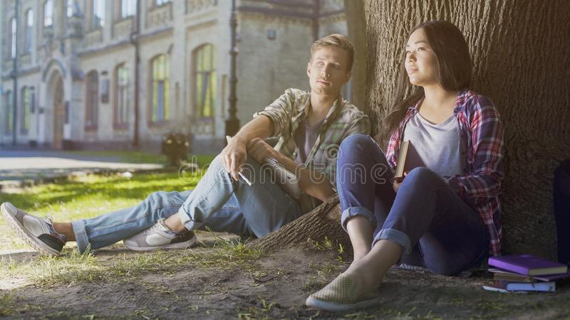 Multiracial male and female students sitting under tree, looking ahead, future royalty free stock image