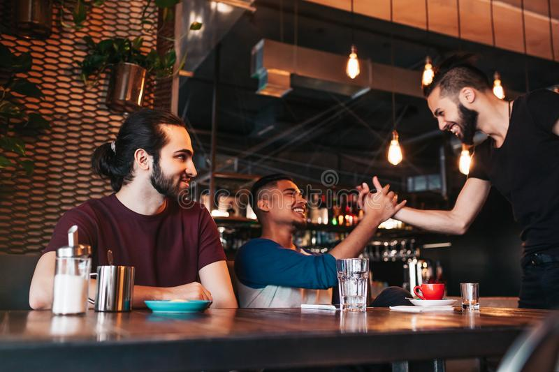 Multiracial men meeting their friend in lounge bar. Real emotions of best friends happy to see each other. Friendship royalty free stock photo