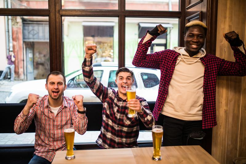 Multiracial men at the pub watcing football game and drinking beer. royalty free stock photo