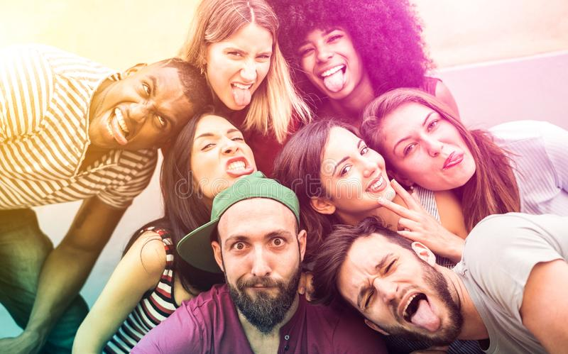 Multiracial millenial friends taking selfie with funny faces - Happy youth friendship concept against racism. With international young trendy people having fun stock photo