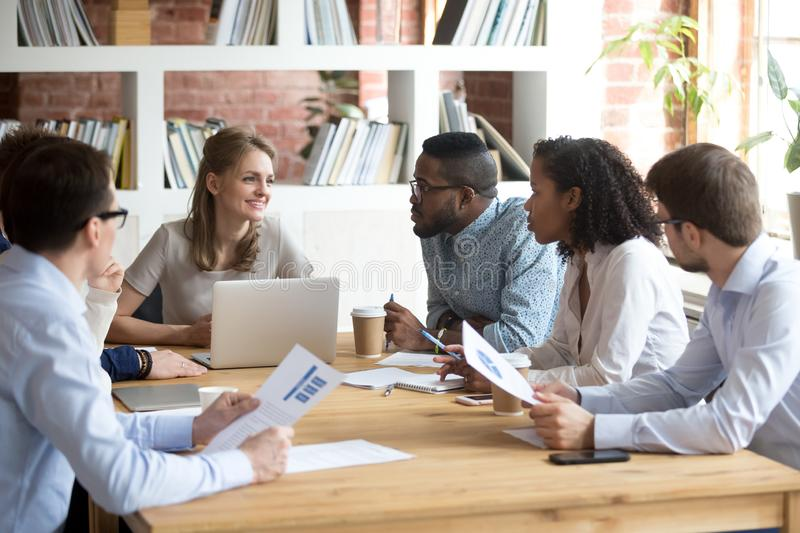 Multiracial colleagues brainstorm during company meeting in offi. Multiracial millennial colleagues brainstorm discussing startup ideas during briefing in stock photos