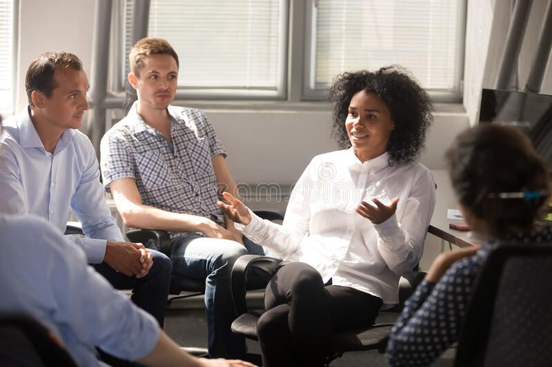 Multiracial colleagues talk during informal briefing in office stock photos