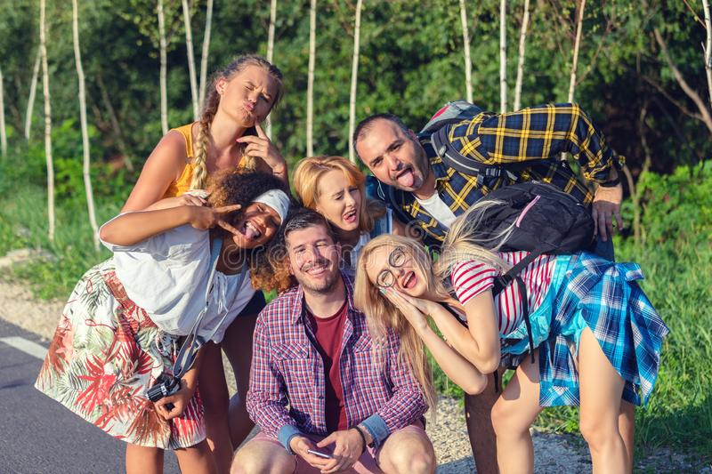 Multiracial millennial friends taking selfie with funny faces while exploring world royalty free stock photography