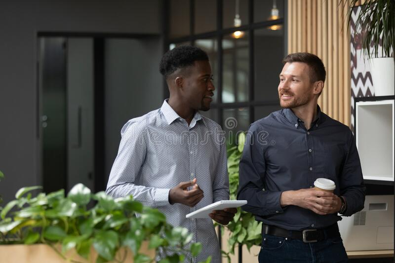 Multiethnic male colleagues stand talking discussing ideas stock image
