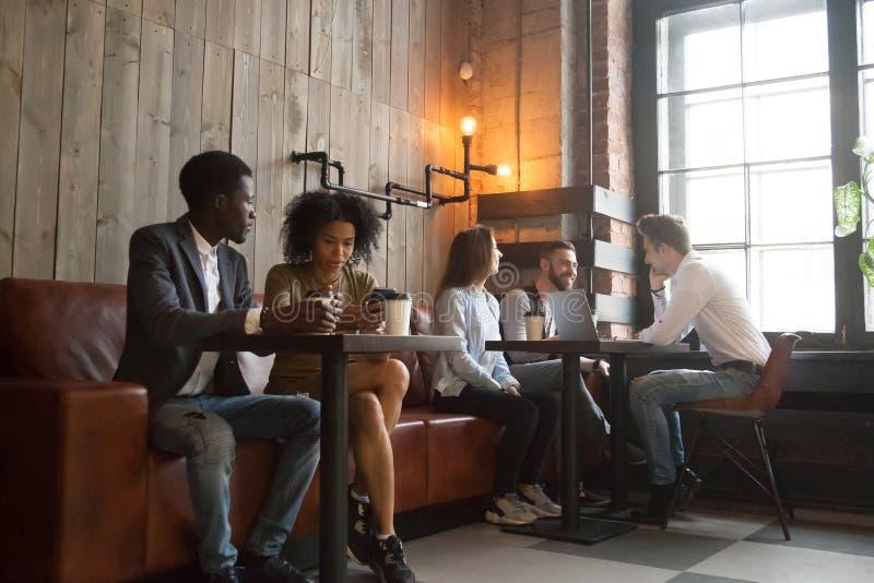 Multiracial millennials cieszy się kawowego działanie na gadżetach w co obraz royalty free