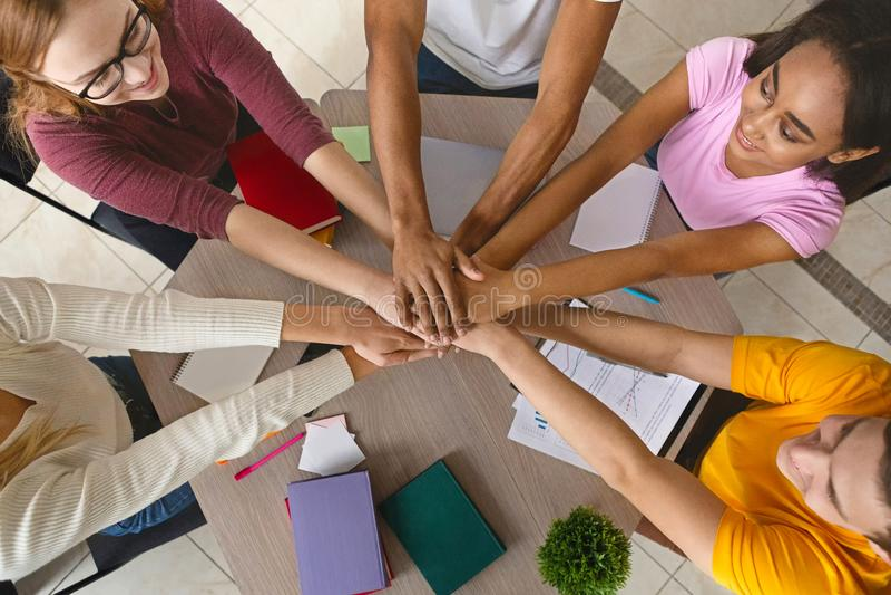 Multiracial nastolatkowie łączy ręki w współpracy wpólnie zdjęcie stock
