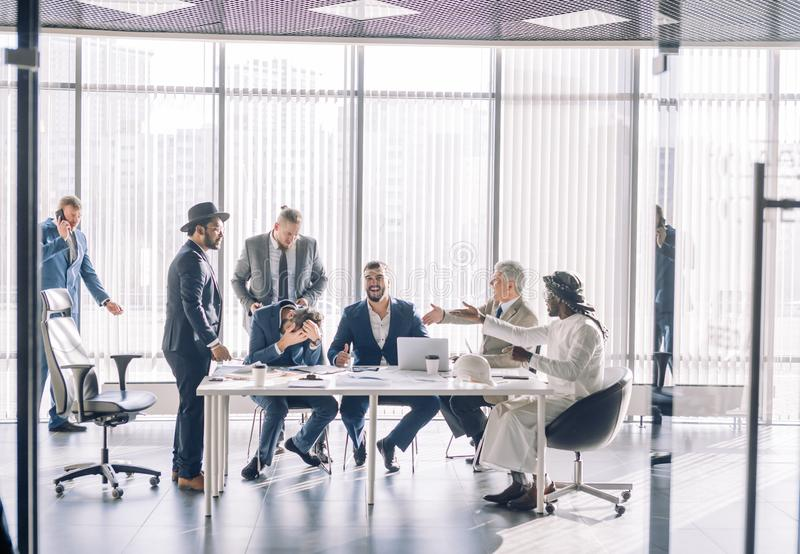 Multiracial partners dispute at negotiations, having fun while settling conflict. Cheeful multiracial group of businessmen having fun during meeting in office stock image