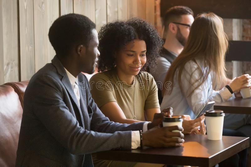 Multiracial people enjoying coffee to go during break in cafe. African American couple spending coffee break enjoying favorite drink in paper cup, using gadgets royalty free stock photography