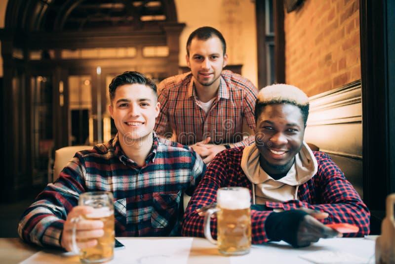 Multiracial przyjaciół pije i wznosi toast grupowy piwo przy pubem Przyjaźni pojęcie z młodzi ludzie cieszy się czas, wpólnie hav zdjęcia royalty free