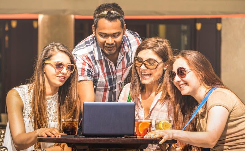 Multiracial przyjaciele przy koktajlu barem ma zabawę z laptopem - Związana społeczność młodzi ucznie zaludnia używać komputer os fotografia royalty free