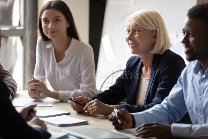 Multiracial smiling businesspeople participating at meeting listening fresh creative ideas stock photo