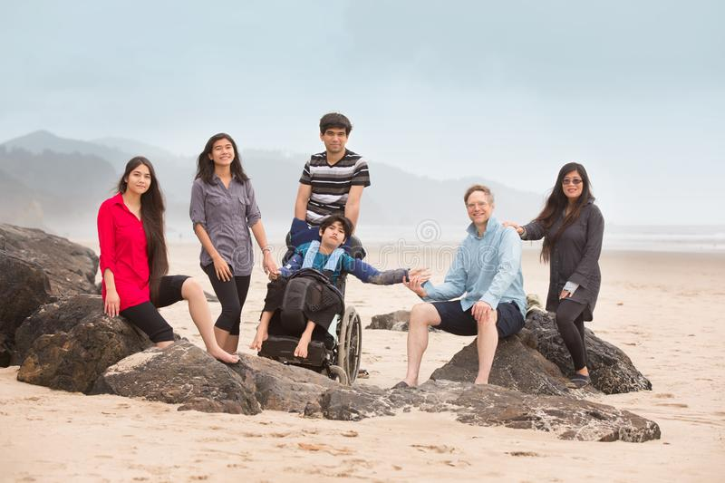 Multiracial special needs family sitting on large rocks along beach royalty free stock photo