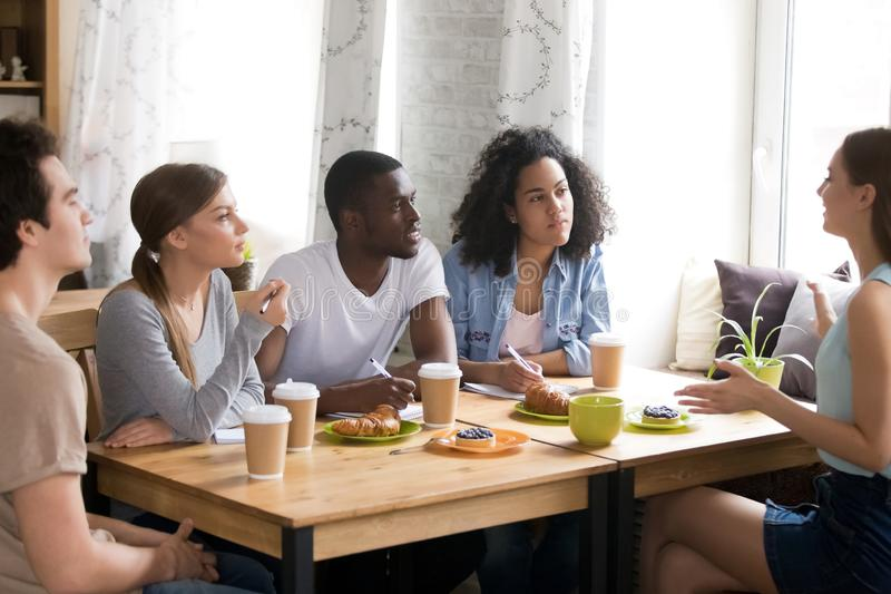 Multiracial students studying together in cafe, brainstorm, share ideas. Thoughts, interested colleagues listening to talking woman, doing exercise homework stock images