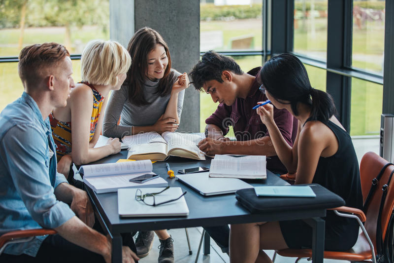 Multiracial students studying together in a library stock photos
