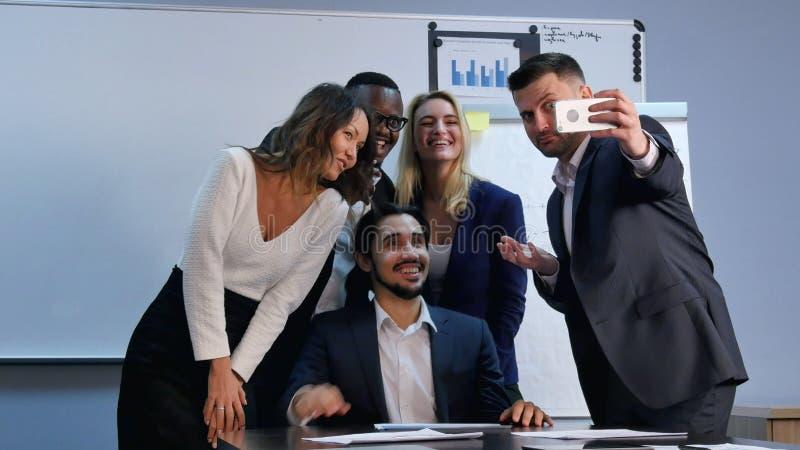 Multiracial team taking selfie at business meeting royalty free stock image