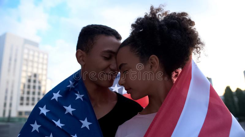 Multiracial teens couple touching foreheads, covered USA flag, tender feelings stock photos