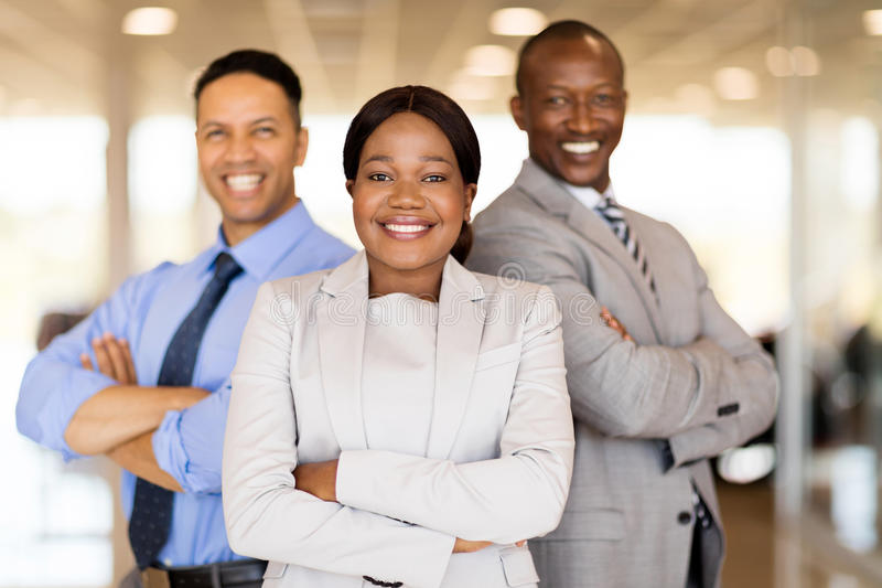 Multiracial vehicle sales team. With arms crossed inside car showroom royalty free stock photography