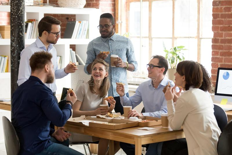 Multiracial work team eating pizza together on break. Multiracial happy work team eating pizza, drinking coffee together on break at shared workspace, having royalty free stock photography