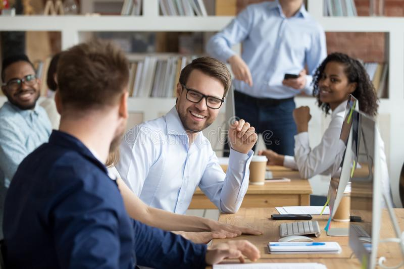 Multiracial work team having fun and laughing together. Employees working and discussing about funny news in shared workspace, teamwork, good relationships in royalty free stock photos