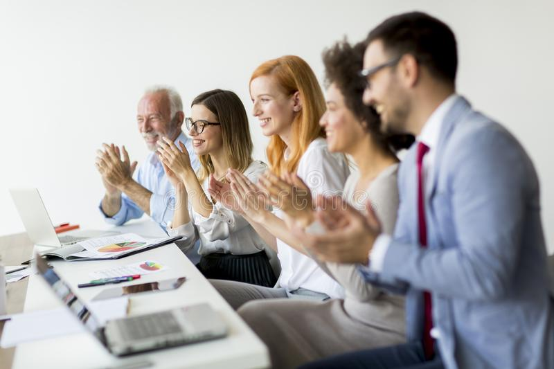 Multiracial young business people clapping hands in office. Multiracial young business people clapping hands in the office royalty free stock photo