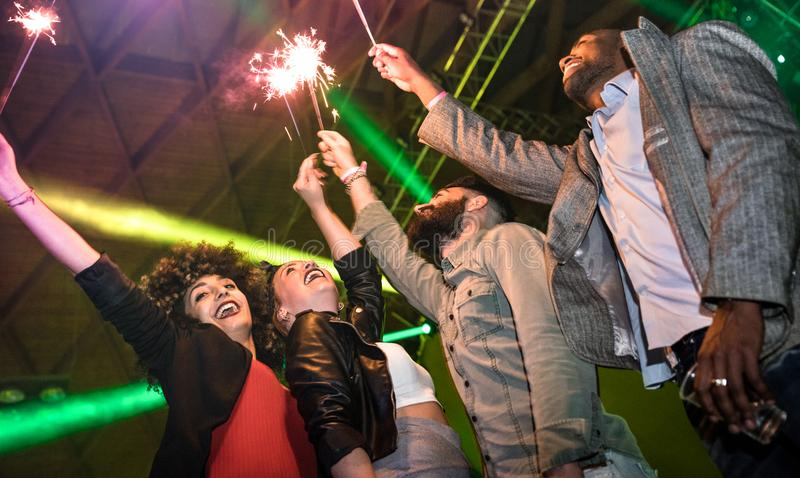 Multiracial young friends dancing at night club with sparkler fireworks - Happy people having crazy fun at nightclub after party stock photo
