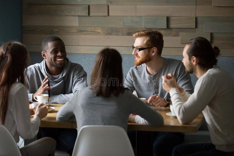 Multiracial millennial friends talking drinking coffee together royalty free stock images