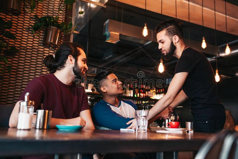 Multiracial men meeting their friend in lounge bar. Real emotions of best friends happy to see each other. Friendship. Multiracial young men meeting their friend royalty free stock photo