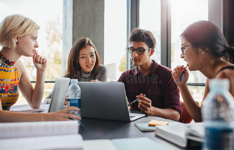 Multiracial young people doing group study at library stock photos