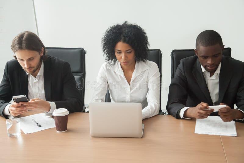 Multiraciale bedrijfsmensen die bij bureaulijst zitten die corpor gebruiken stock afbeeldingen