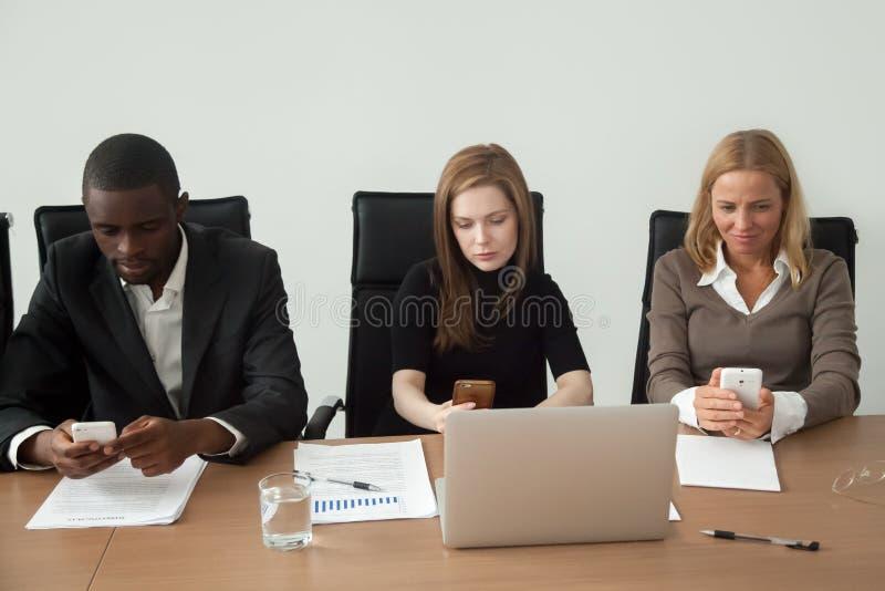Multiraciale bedrijfsmensen die gebruikend mobiele telefoons bij groep houden stock fotografie
