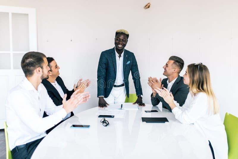 Multiraciale bedrijfsmensen die zitting toejuichen bij conferentielijst, divers team die handen na groepsvergadering slaan multin royalty-vrije stock foto