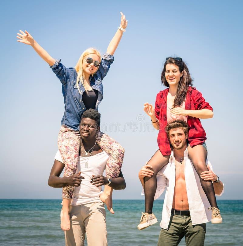 Multiraciale beste vrienden bij strand die pret met vervoer per kangoeroewagenspel hebben stock foto's