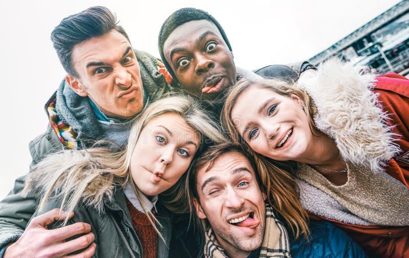 Multiraciale beste vrienden die in de herfst winterkleding selfie buitenshuis nemen - Happy youth concept met milleniummensen die stock foto