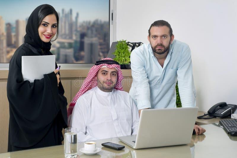 Multiraciale Commerciële Vergadering in bureau, Arabische zakenman & Arabische Secretaresse hijab & een Vreemdelingsvergadering d royalty-vrije stock afbeeldingen