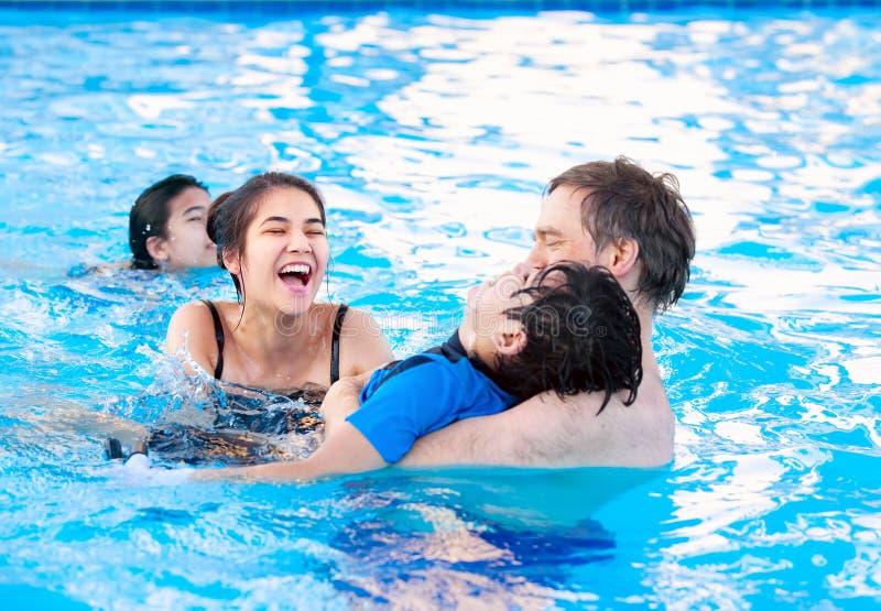 Multiraciale familie die samen in pool zwemmen Gehandicapte het jongst royalty-vrije stock foto's