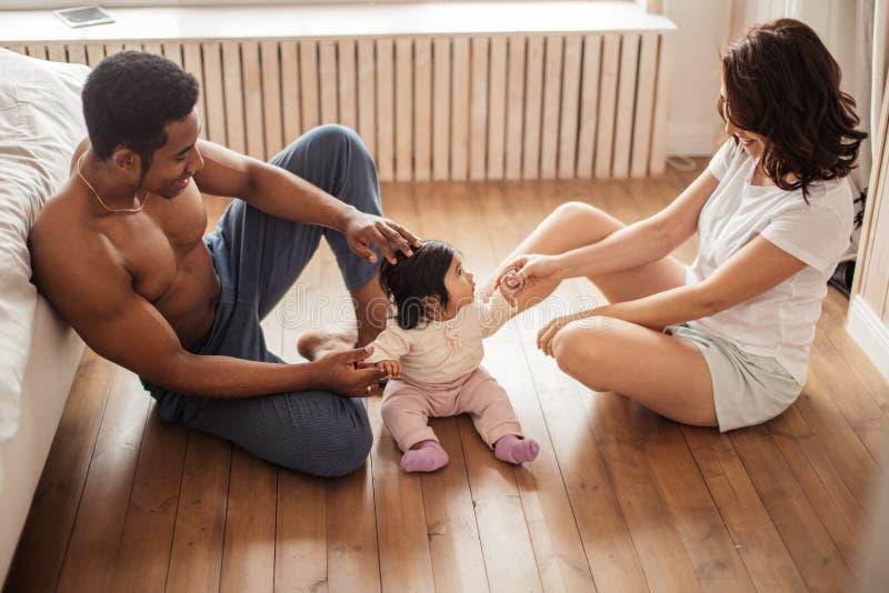 Multiraciale familie het besteden tijd met hun aanbiddelijke baby royalty-vrije stock foto