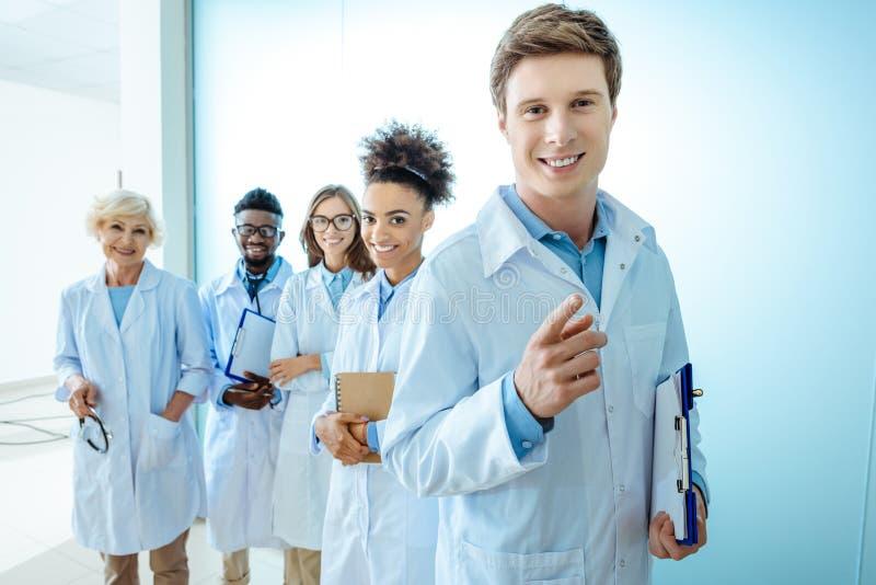 Multiraciale groep glimlachende medische internen in laboratoriumlagen die zich op een rij met klemborden bevinden royalty-vrije stock fotografie